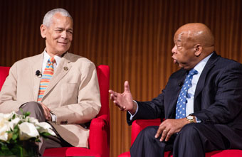 Julian Bond and John Lewis seated in red chairs talking