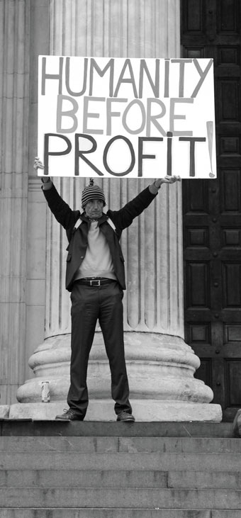 "Man holding sign that says ""humanity before profit"""