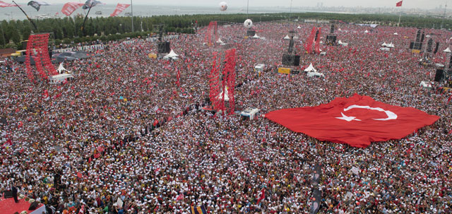 Crowd of people with giant Turkish flag