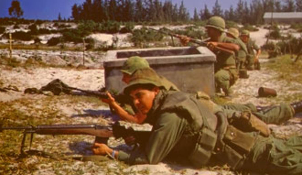 Soldiers aiming rifles laying on ground