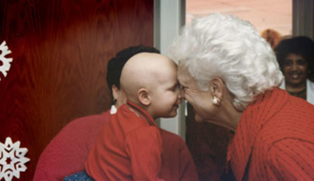 Barbara Bush interacting with a child undergoing cancer treatment