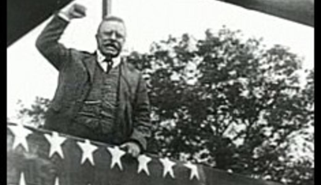 Theodore Roosevelt at a rally with fist raised