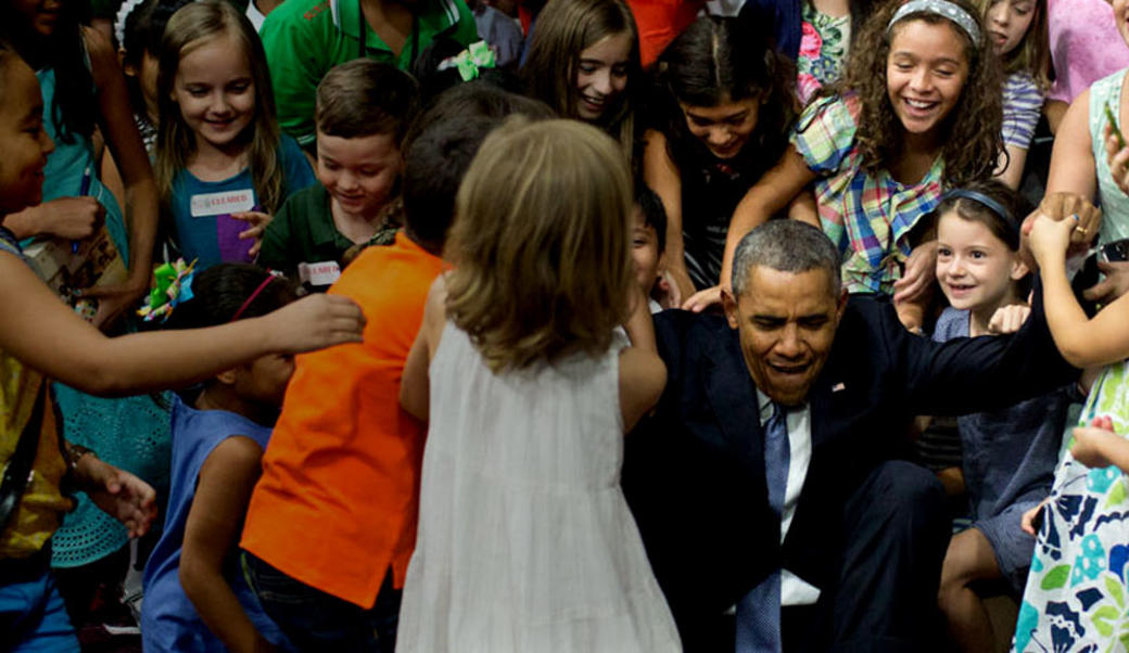 President Obama with a group of children, his arms outstretched