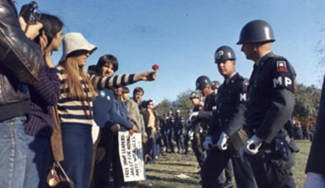 1960s hippie offering a flower to an MP
