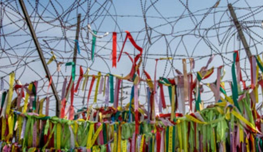 Buddhist peace flags on barbed wire