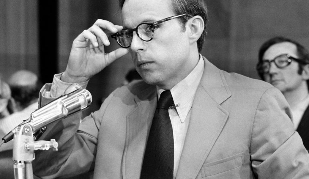 John Dean in front of a mic reaching up to touch his glasses