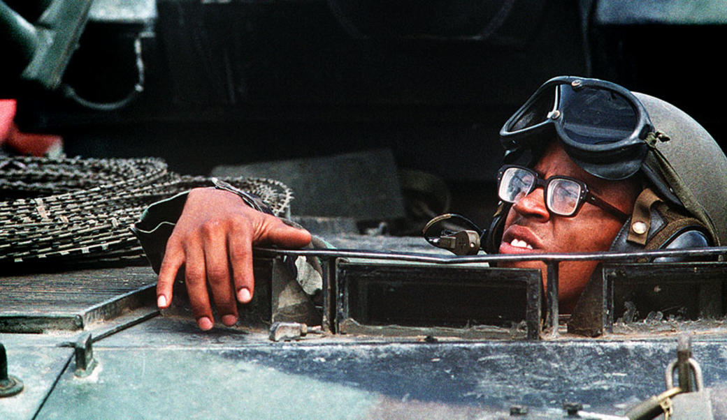 Marine looking out of hatch of armored personnel carrier