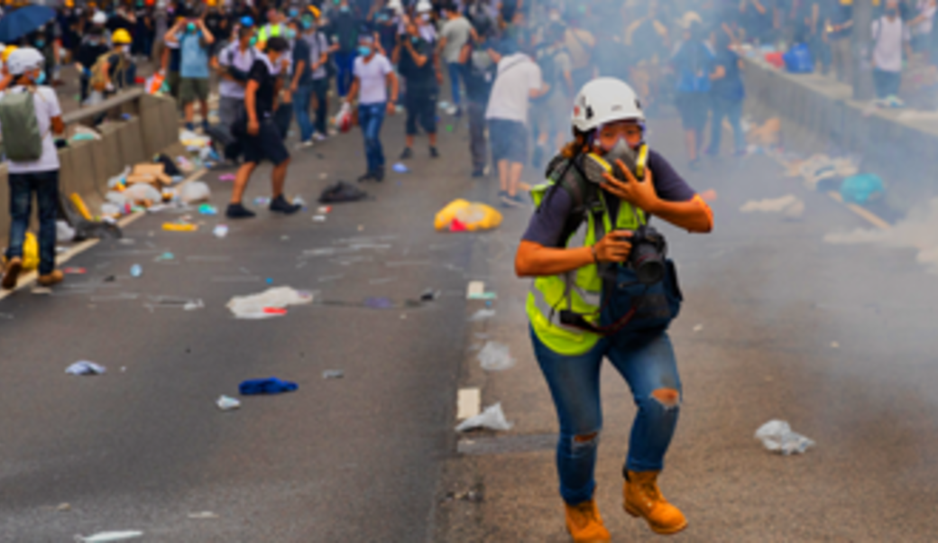 Protestor covering her mouth with tear gas swirling