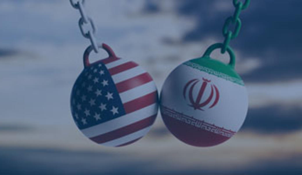 Wrecking balls with Iran and US flags painted on them colliding