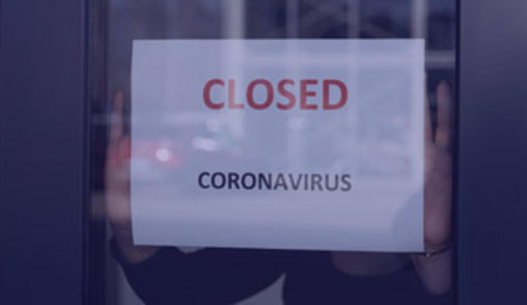Shopkeeper posts a sign that a business is closed due to coronavirus