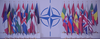 Members of NATO and their flags surround the NATO symbol