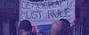 Protesters in London with a sign that says 'Democracy must rule'