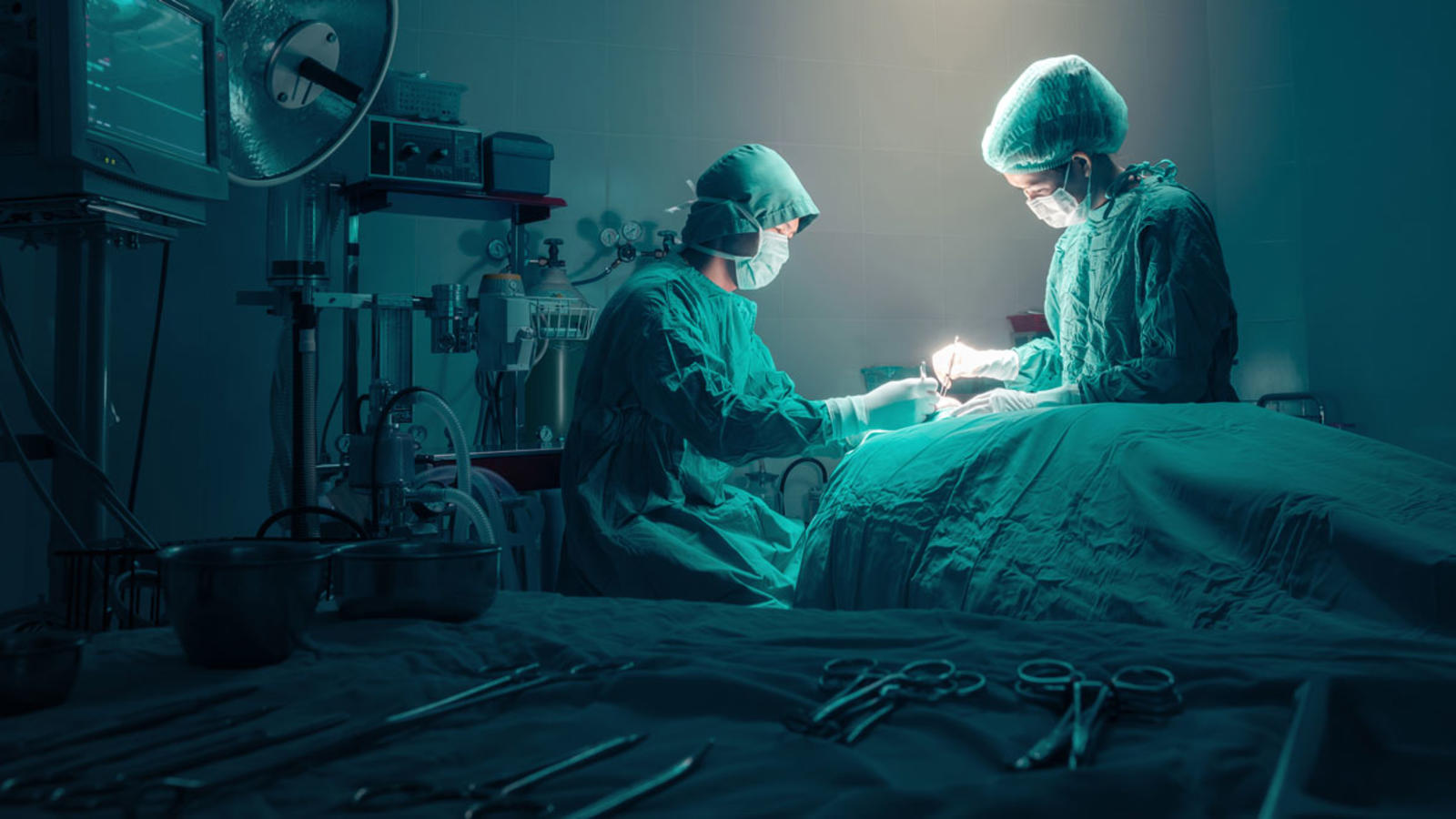 Doctors preforming surgery in a dimly lit operating room